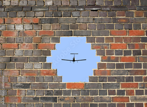 canvas print picture Small plane through a hole in a brick wall