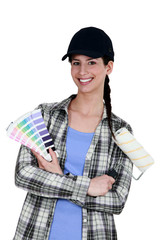 female painter holding a roller brush and a color chart