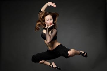 Молодая красивая женщина прыгает на изолированном черном  фоне.