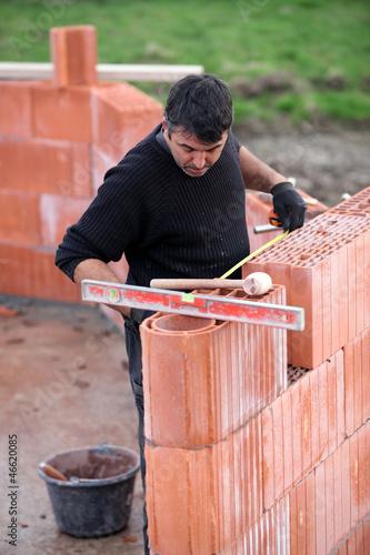 bricklayer erecting red brick wall