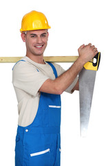 Workman carrying timber and a saw