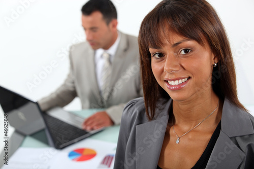 businesswoman standing in front of a colleague with laptop