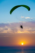 Silhouette of a paraglider at sunset