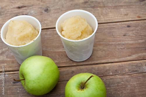Apple sorbet and apples on wooden table