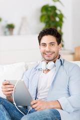 lächelnder mann hört musik mit tablet