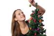 Frau schmückt einen Christbaum