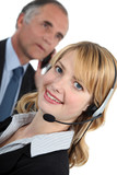 young receptionist with headset and boss in background