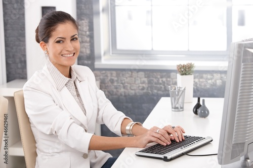 Happy office girl working on computer