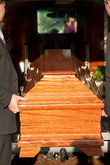 Funeral with casket carried by coffin bearer