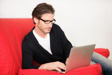 Junger Mann mit Laptop auf der Couch