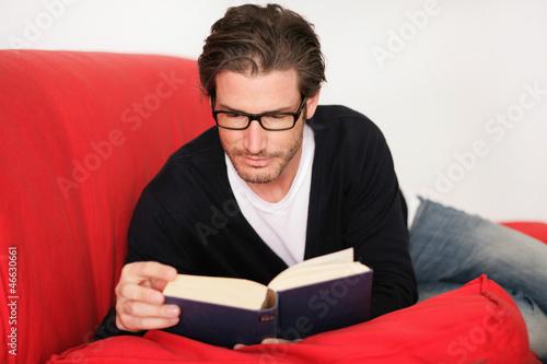 Junger Mann beim Lesen auf dem Sofa