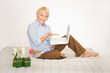 Ältere Dame mit Laptop auf dem Bett