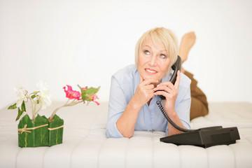 Frau telefoniert auf dem Sofa