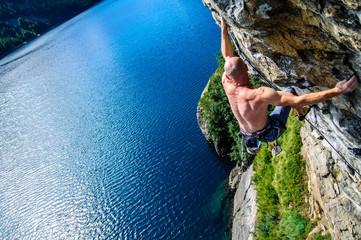 Climber climbing a rock wall above Lake Devero, Northern Italy