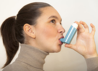Cute young female using an asthma inhaler