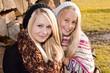 Zwei Schwestern vor Holzstapel