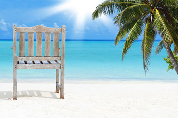 Holzstuhl am Strand auf den Malediven mit Sonne