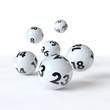6 Lottokugeln rollen auf weißem Hintergrund
