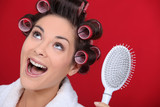 Excited brunette wearing hair-rollers