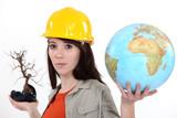 Woman holding a dead bonsai and a globe