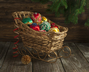 Vintage handmade Christmas ornaments in decorative sledge.