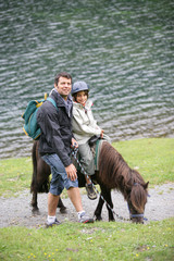 Man taking a child for a pony ride