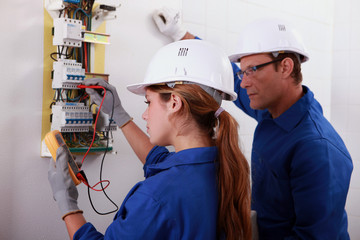 Man and woman measuring voltage