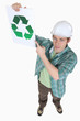 Builder pointing at recycle poster