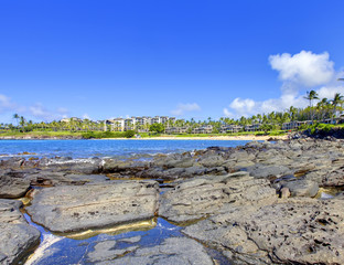 Island Maui lava beach with resort buildings on the back.