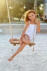 little girl sitting on a swing