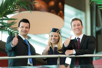 Stewardess und Business-Männer zeigen Daumen hoch