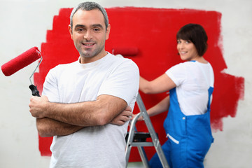 Couple repainting home walls in red