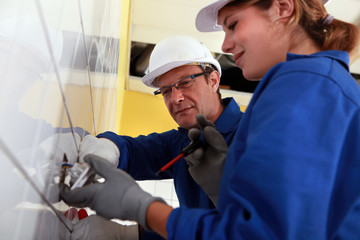 a young female electrician and a mature electrician