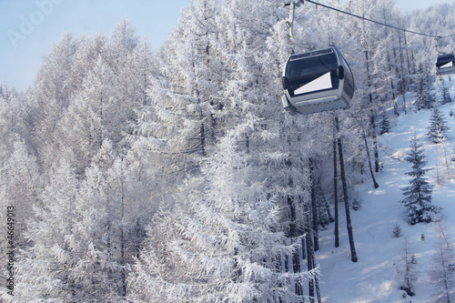Chair lift between beautiful firs in winter mountains