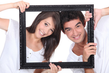 Couple holding empty picture frame