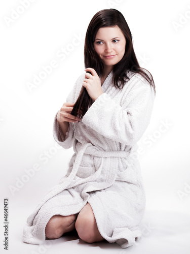 Pretty young woman in bathrobe sweeps trough her hair