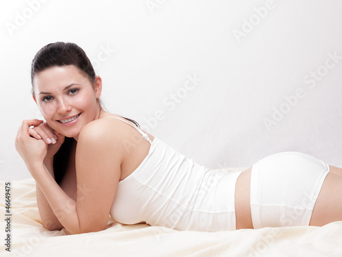 Pretty young woman lies on her stomach in her bed