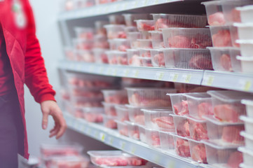 Customers selecting beef and pork slices on shelves in supermark