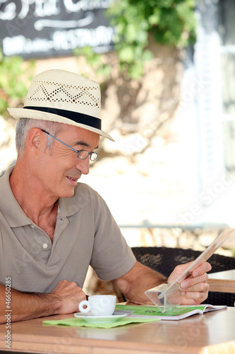 Elderly man sat drinking coffee on terrace