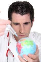 Doctor using syringe on a globe