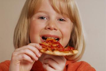 Pequeña niña comiendo pizza.