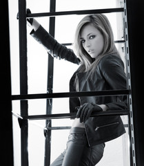 A young and fit woman posing in black leather clothes