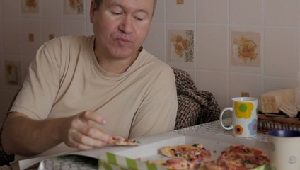 man eats pizza