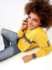 Joven casual estilo afro al teléfono.