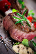 Bloody bbq steak with fresh herbs and tomatoes