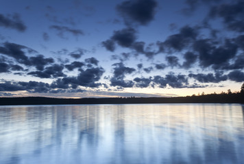 Lake in twilight, long exposure with blurred clouds and water
