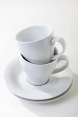 Weisse Kaffeetassen mit Untersetzer