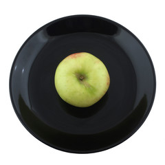 green apple on black plate isolated on white background