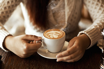 woman hands with latte on a wood table