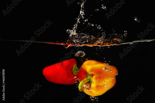 Fresh red and yellow bellpepper falling into the water